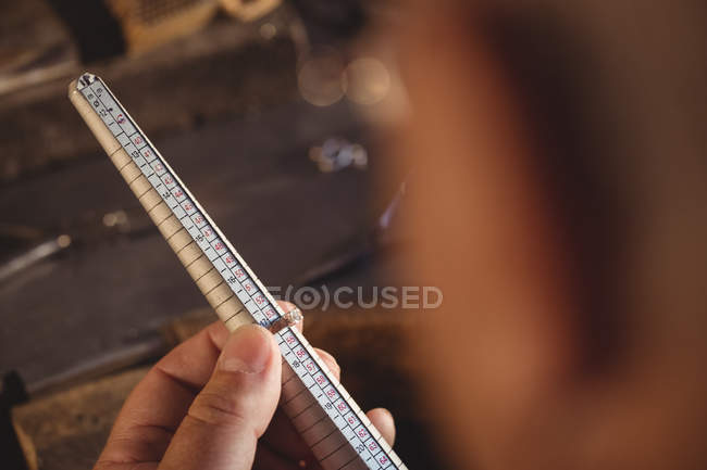 Close-up of goldsmith measuring ring in workshop — Stock Photo