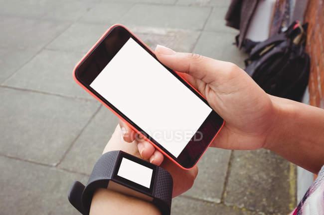 Кадроване зображення людини, що використовує наручні годинники тримаючи телефон — стокове фото