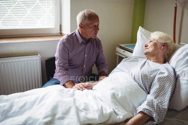 Senior man consoling senior woman in hospital ward — Stock Photo