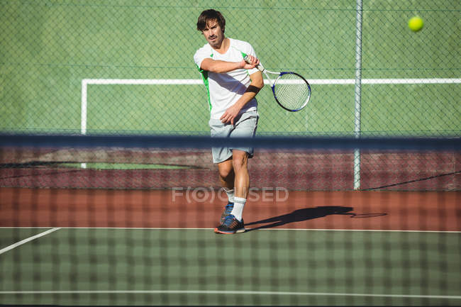 Homem jogando tênis na quadra de esporte à luz do sol — Fotografia de Stock
