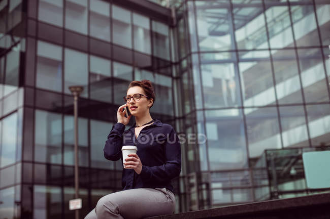 Young woman talking on mobile phone against modern building — Stock Photo