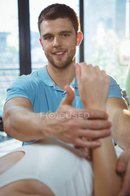 Male physiotherapist giving arms massage to female patient in clinic — Stock Photo
