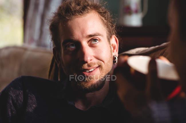 Lächelnde junge Mann sitzt zu Hause auf sofa — Stockfoto