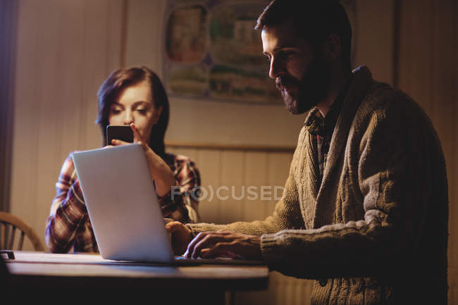Couple using laptop and mobile phone at home — Stock Photo