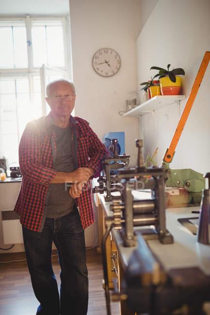 Ritratto di goldsmith in piedi accanto a mano al laminatoio in officina — Foto stock