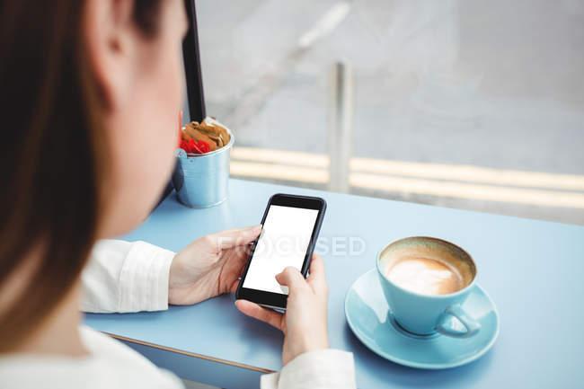 Immagine potata di messaggi sul cellulare nella caffetteria di testo di donna — Foto stock