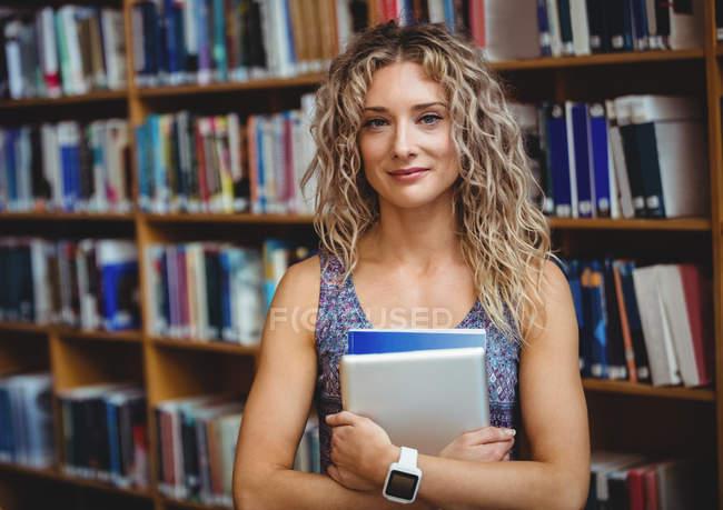 Portrait de femme tenant la tablette numérique en bibliothèque — Photo de stock