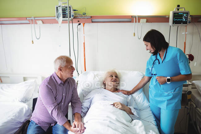 Senior couple interacting with nurse in hospital — Stock Photo