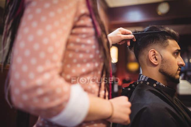 Uomo ottenere i capelli tagliati in negozio di barbiere — Foto stock