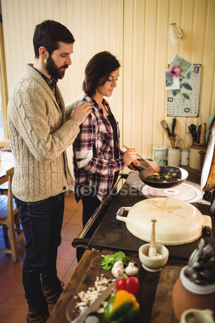 Couple preparing food together in kitchen at home — Stock Photo