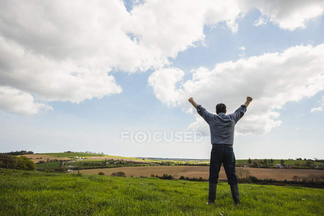 Full length of man standing with arms raised against cloudy sky — Stock Photo
