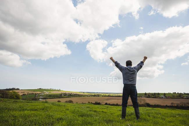 Повна довжина людину, стоячи з руки підняла проти хмарного неба — стокове фото