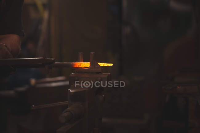 Hand of blacksmith working on a heated iron rod in workshop — Stock Photo
