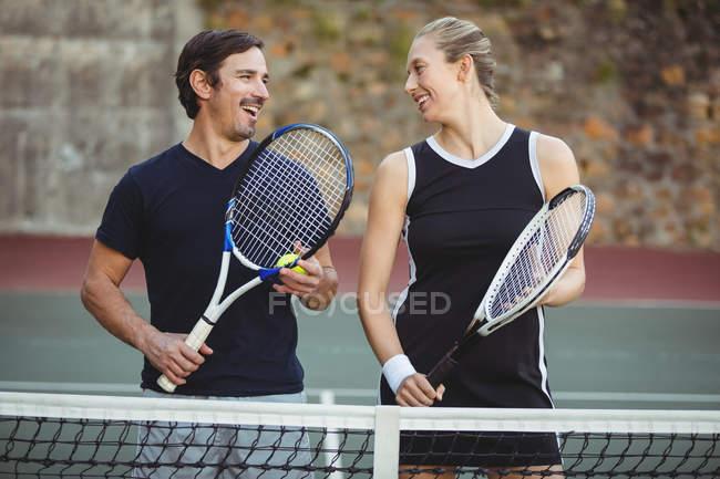Jugadores de tenis feliz de pie en la corte con raquetas - foto de stock