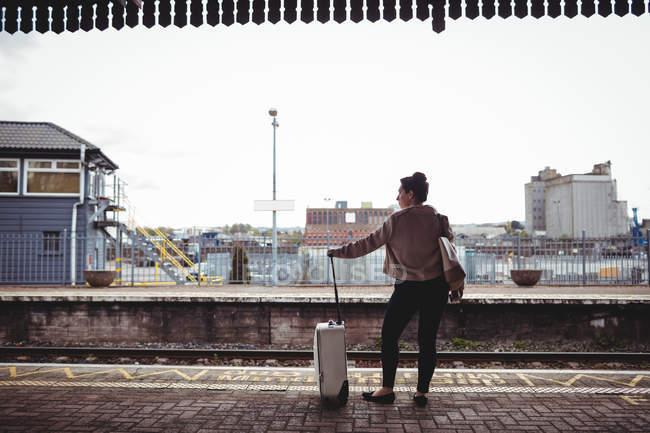 Полная длина женщины, стоящей на платформе железнодорожного вокзала — стоковое фото