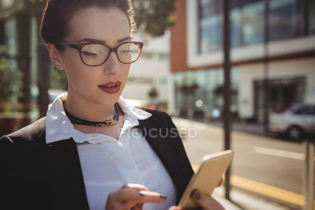 Bella donna d'affari che utilizza il telefono cellulare su strada — Foto stock