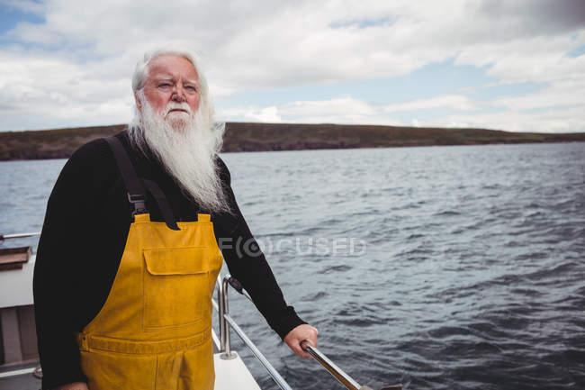 Thoughtful fisherman looking at sea from fishing boat — Stock Photo
