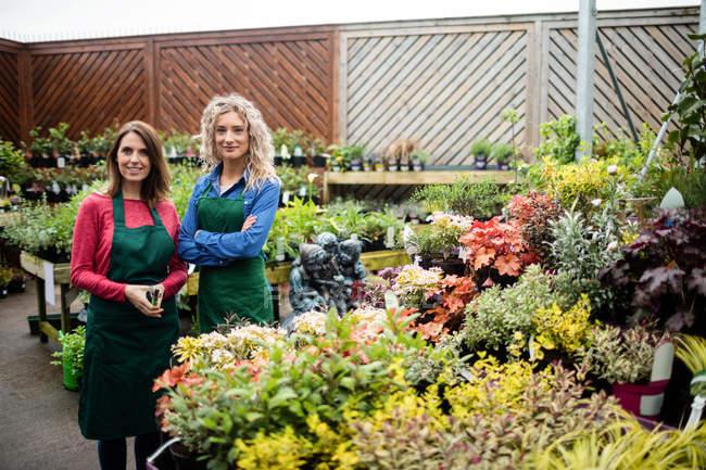 Портрет жіноче флористів, посміхаючись в садовому центрі — стокове фото