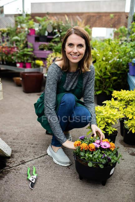 Портрет щасливі жіночий флорист з рослин горщиків в садовому центрі — стокове фото