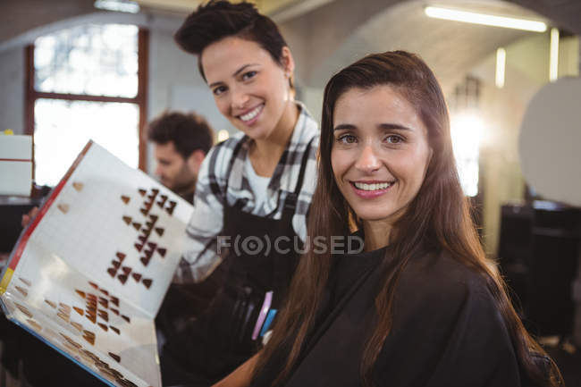 Portrait de femme souriante sélectionnant la couleur des cheveux avec le styliste au salon de coiffure — Photo de stock