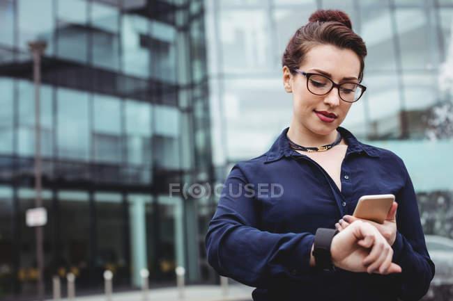 Деловая женщина, использующая мобильный телефон возле офисного здания — стоковое фото