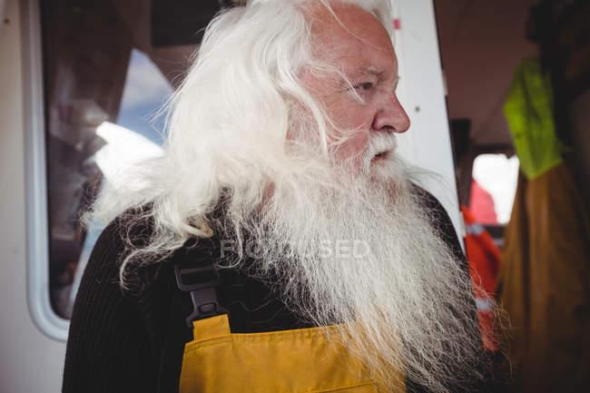 Portrait of senior thoughtful fisherman in boat — Stock Photo