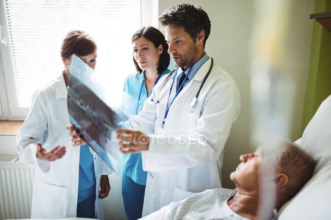 Médicos interagindo sobre relatório de raio-x com o paciente no hospital — Fotografia de Stock