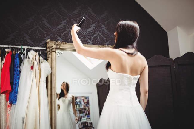 Mulher tomando selfie ao experimentar o vestido de noiva em estúdio — Fotografia de Stock