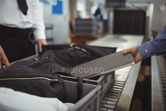 Homem colocando portátil em bandeja para verificação de segurança no aeroporto — Fotografia de Stock