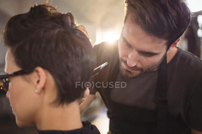 Mujer consiguiendo su pelo recortado en salón - foto de stock