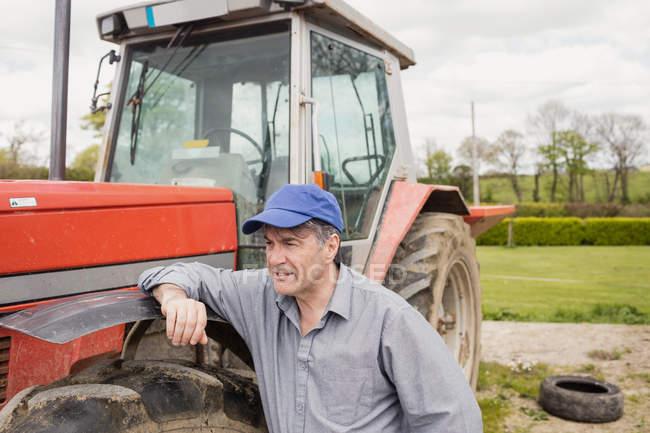Landwirt stützt sich auf Traktor auf Feld — Stockfoto