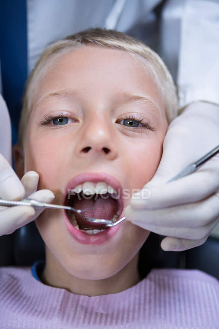 Dentist examining a young patient with tools at dental clinic — Stock Photo