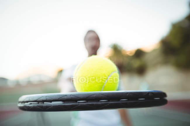 Primer plano de la pelota de tenis y raqueta de jugador en la corte - foto de stock