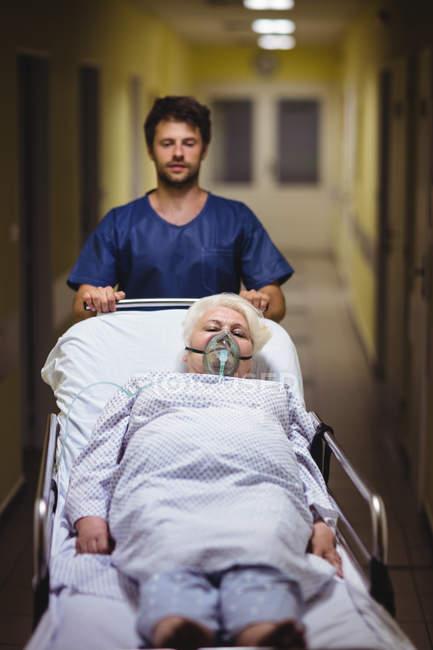 Ward boy empujando paciente senior en camilla en el pasillo del hospital - foto de stock