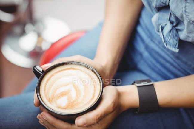 Sección media de la mujer con taza de café en el restaurante - foto de stock