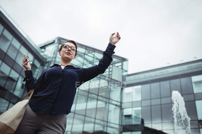 Low angle view of businesswoman gesturing outside office — Stock Photo