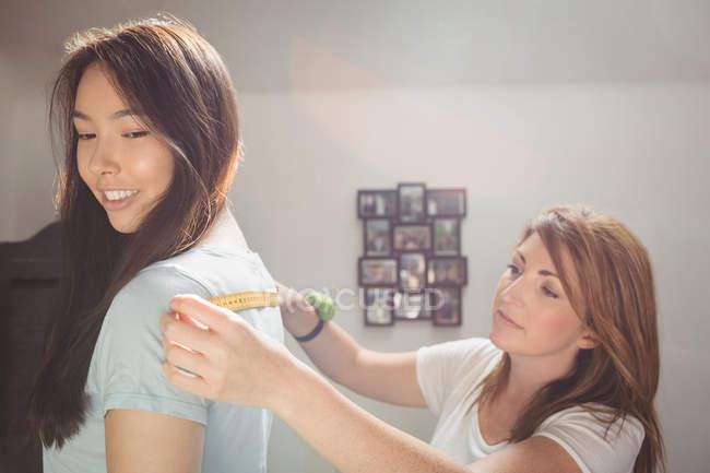 Fashion designer measuring woman shoulders in studio — Stock Photo