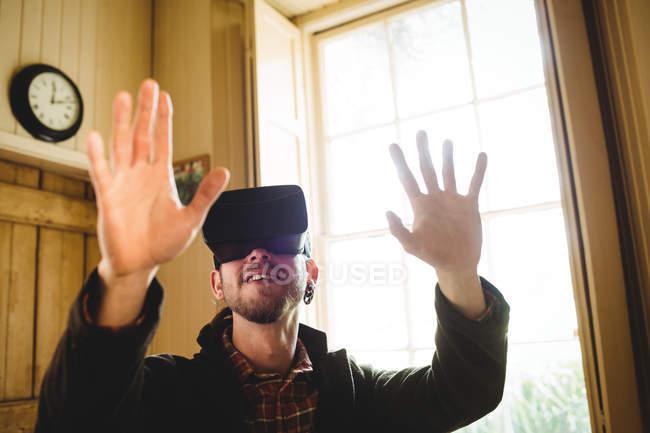 Close-up of young man gesturing while using virtual reality simulator at home — Stock Photo