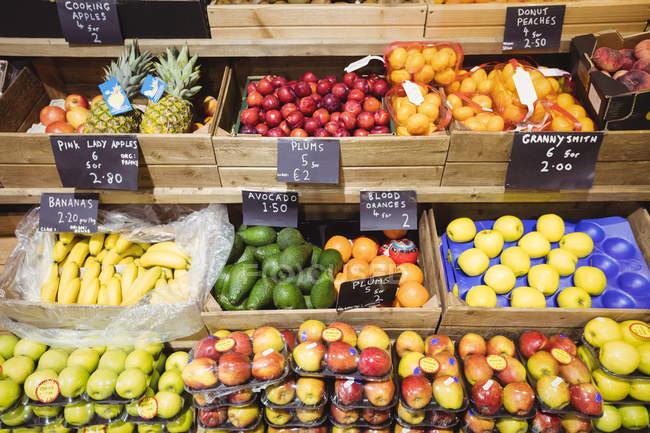 Variedade de frutas em caixas de madeira no supermercado — Fotografia de Stock