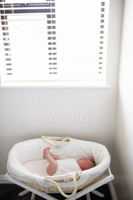 Newborn baby sleeping in moses basket at home — Stock Photo