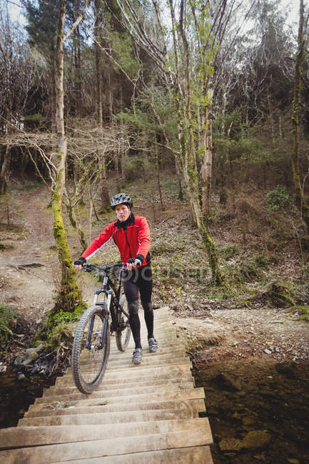 Front view of mountain biker walking with bicycle on foot bridge in forest — стоковое фото