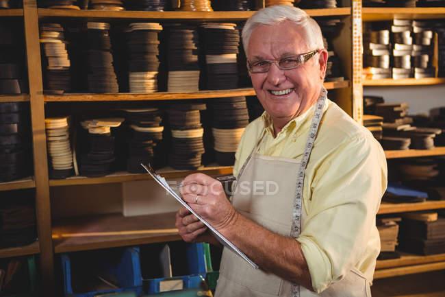 Zapatero Senior en portapapeles en taller de escritura - foto de stock