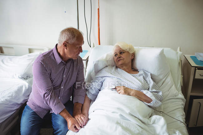 Senior man consoling senior woman in hospital — Stock Photo