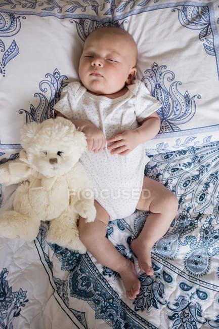 Vista superior del bebé durmiendo en la cama con oso de peluche en el dormitorio - foto de stock