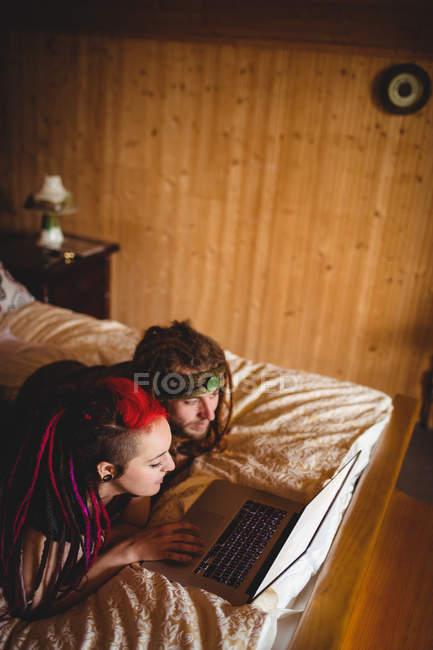 Висока кут зору hipster молода пара використання ноутбука на ліжку у себе вдома — стокове фото
