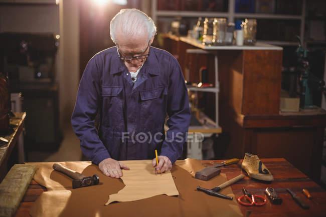 Sapateiro cortando um pedaço de couro na oficina — Fotografia de Stock