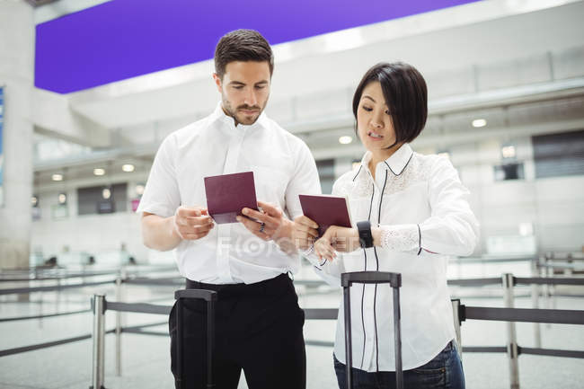Uomo e donna d'affari che controllano i passaporti nel terminal dell'aeroporto — Foto stock
