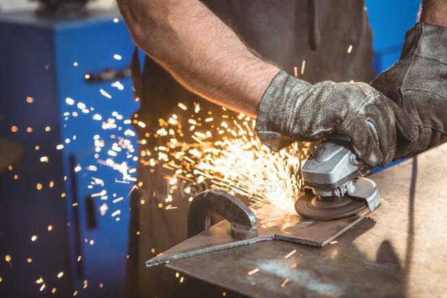 Обітнутого зображення зварювальник різання металу з електричним інструментом в майстерні — стокове фото