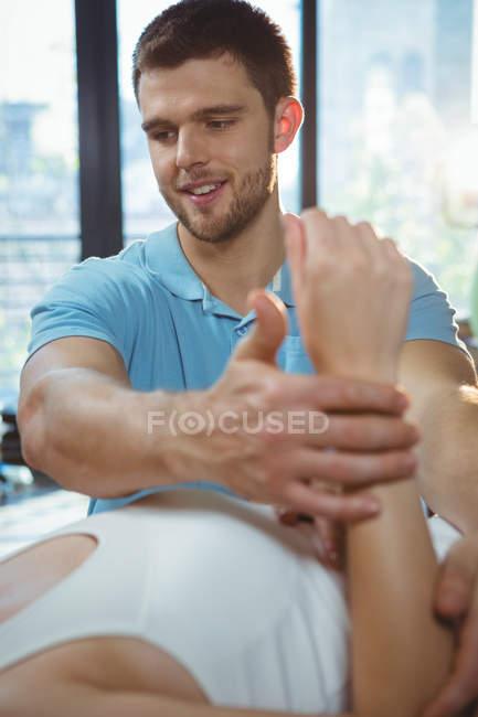Мужской физиотерапевт, делающий массаж рук пациентке в клинике — стоковое фото