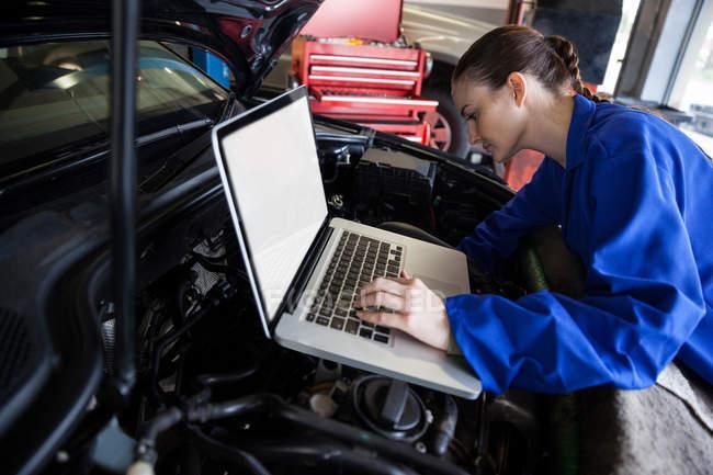 Mecánica femenina que utiliza una tableta digital durante el mantenimiento del motor del coche en el garaje de reparación - foto de stock